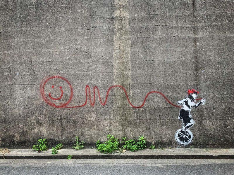 一輪車に乗りながら壁にスプレーでらくがきをする子供